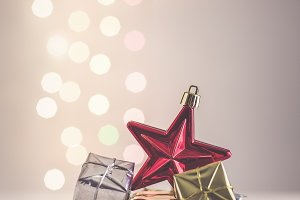 Christmas still life with red star and gifts on background lights