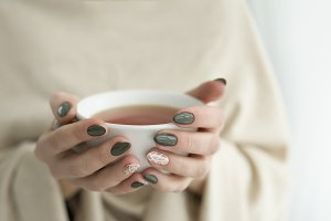 well-groomed hands with a cup of tea