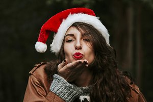 young woman with santa claus hat kissing