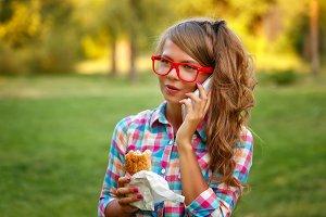 Girl speaks on phone, hold hotdog