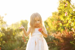Nice little girl eating a tomato.
