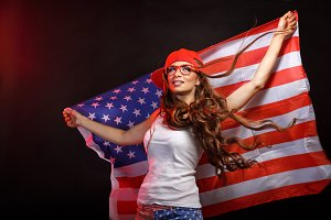 Girl in baseball cap holding US flag