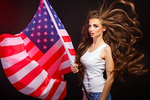 Girl holding US flag on a flagpole
