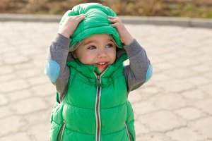 Boy corrects hooded jacket.