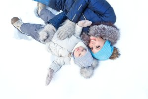 Mother and daughter lying on snow