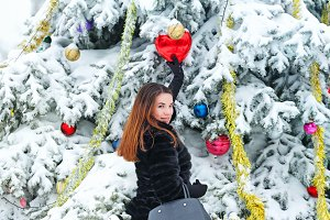 Girl decorates Christmas tree balls