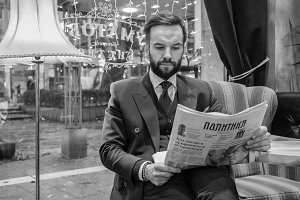 Man in suit reading papers