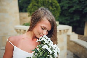 Girl smelling a bouquet of daisies