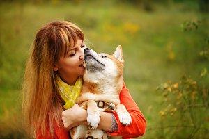 Girl hugging dog Shiba Inu