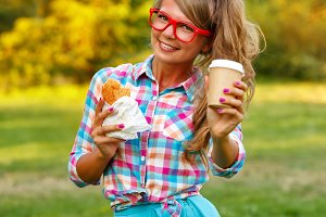 Girl holds cup of coffee and hot dog