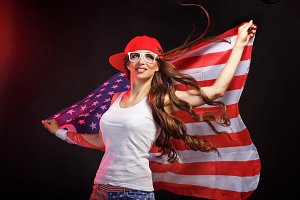 Girl in baseball cap hold US flag