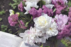 White peony and spirea with a book