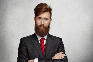 Business, success and achievement concept. Portrait of attractive successful confident young businessman or corporate worker with stylish haircut and thick beard standing isolated with arms folded