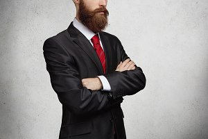 Cropped shot of good-looking confident and successful bearded entrepreneur standing with arms crossed, thinking of important business deal. Isolated portrait of handsome man on gray background