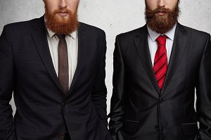 Cropped shot of two Caucasian bearded entrepreneurs dressed in formal suits, standing with hands in pockets during business meeting in office. Two young colleagues or partners having agreement