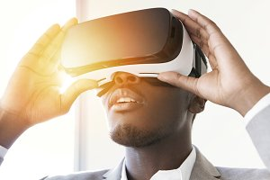 Portrait of astonished African office worker or businessman using oculus rift headset, experiencing virtual reality while playing video game, holding hands on goggles, looking joyful. Flare sun