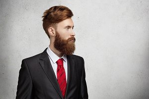 Midsection of young handsome Caucasian office worker or freelancer with stylish beard and haircut dressed in elegant suit looking away at blank wall with copy space for your information in studio