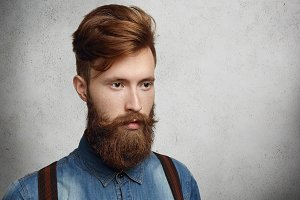 Fashionable young student with stylish haircut spending time indoors, standing against copy space wall for your promotional content. Hipster model looking thoughtful and serious posing in studio