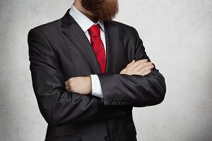 Cropped view of attractive successful entrepreneur with thick beard standing with arms folded in office, thinking of something important. Picture of serious confident man. Horizontal, isolated on gray