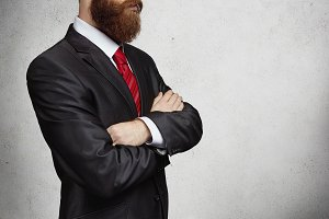 Business style concept. Cropped image of fashionable Caucasian young bearded businessman holding arms crossed while standing against gray background with copy space for your promotional content