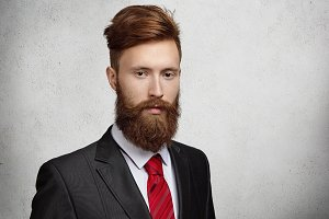 People, career, business and success concept. Headshot of young successful bearded businessman wearing formal suit with red tie looking thoughtful and concentrated during working day at office