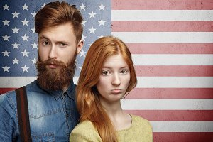 Unhappy Caucasian family couple looking upset, having conflict or dispute, going through hard times. Young bearded husband angry and mad at his redhead wife posing on American flag background