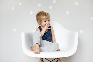 Cute little blonde barefooted preschool boy in sleeping suit looking suprised and amazed, covering his mouth, sitting on white chair against studio wall background with copy space for your content