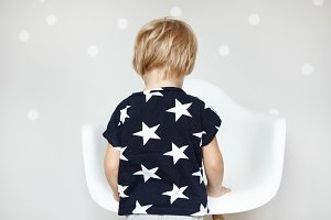 Little playful Caucasian boy with blonde hair dressed in t-shirt with stars, playing with his toys in nursery. Rear view of adorable sweet toddler in front of white chair at home. Horizontal