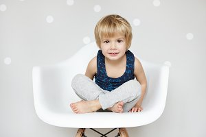 Portrait of cute Caucasian infant with blonde hair and big beautiful eyes dressed in sleeping suit, sitting with legs crossed on white chair, staring and smiling at camera, refusing to go to bed