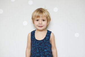 Studio shot of adorable blonde male toddler with fair hair and beautiful brown eyes, looking at camera with his childish smile, standing against white wall with copy space for your promotional content