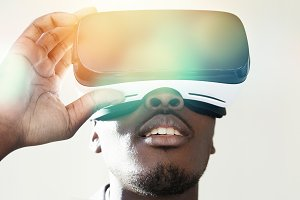 People, technology, cyberspace and entertainment concept. Close up of drak-skinned man wearing 3d headset, playing video games. Black male experiencing virtual reality, using oculus glasses. Flare sun