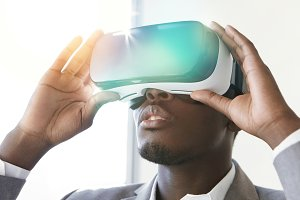 Technology and entertainment. African employee dressed in suit, experiencing virtual reality, wearing VR headset glasses in office. Amazed black man using head-mounted display, playing video games