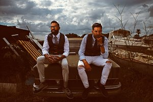 Elegant men sitting on vintage car