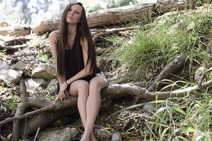 Nature girl sitting on a tree root