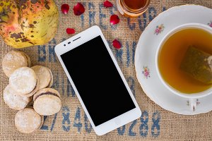 Smartphone with tea and cookies