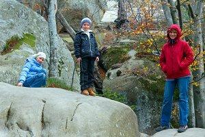 Happy family in autumn stony forest