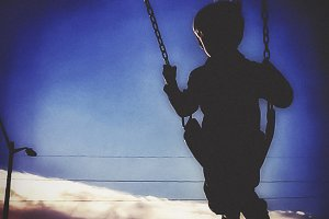 Silhouette of Boy Swinging at Sunset