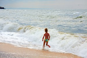 Small girl near summer sea