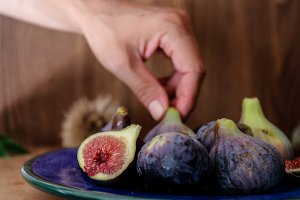 Hand picking fig from ceramic plate