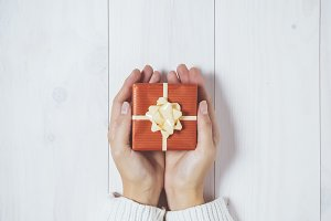 Woman holding a christmas gift on white wooden background