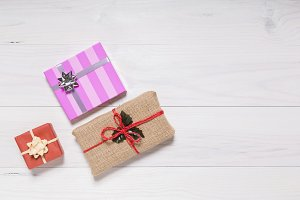 Still life christmas gifts on white wooden background