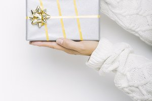 Woman holding a Christmas gift on white background