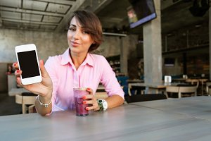 Girl showing her phone in cafe