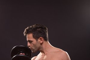man kissing dumbbell weights body