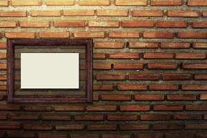 Blank photo frame on the brick wall