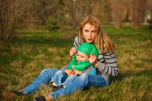 Mother and son sitting on lawn