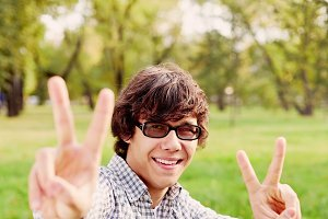 Teenager showing V signs in park