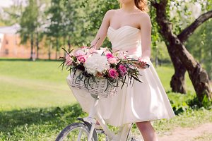 young bride in white dress and with a bouquet in the summer