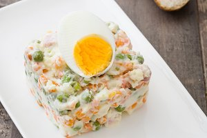 Russian salad on wooden table