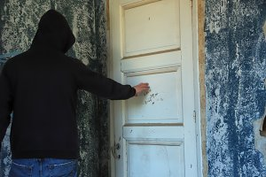 Hooded Figure Closed Door